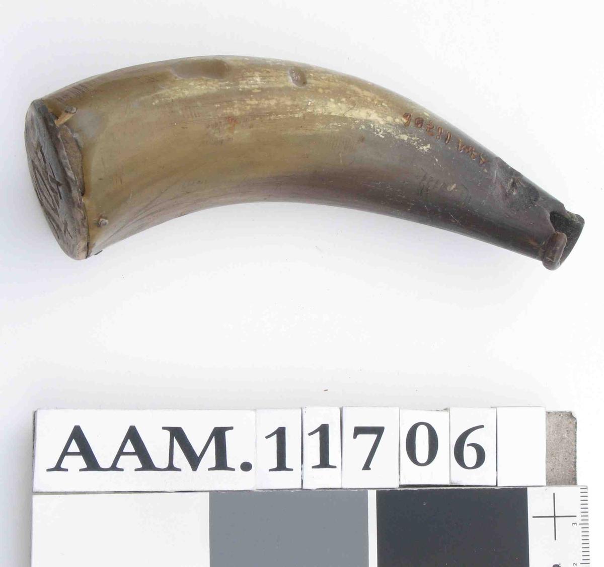 Lite horn med oval topp plate av tre  med innrissede bokstaver. Bunnpropp mangler.