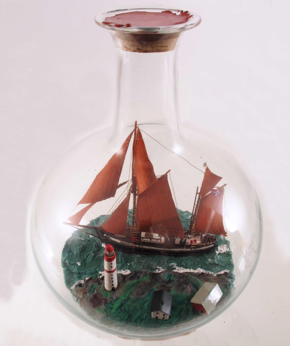 """Galeasen """"Toftevåg""""  bygget 1910,  med rødbrune seil  midt i flasken, på den ene side Torungen fyr med to små bygninger ved siden.  Skuta er solgt ut av landet. Giver har laget denne i et eks."""