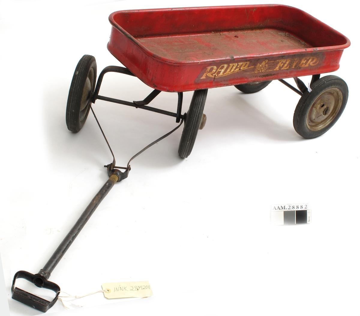 Vogn av metall, rød,  med fire hjul, svingbare forhjul, lasteplan avrundet  Hjul med gummi. Lasteplanet har rektangulær form med avrundede hjørner, Lasteplan er rød, hjulene grå, resten sort. Kan ha fått et malingstrøk.