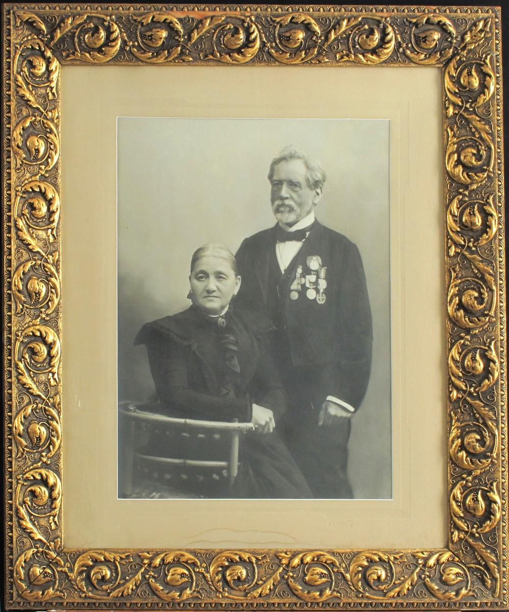 Portrett av et ektepar, hun sittende på stol, mannen står ved hennes venstre side. Hun ikledd mørk kjole med rysjer og  brosje i halsen, han i dress med tversoversløyfe og mange medaljer på brystet.