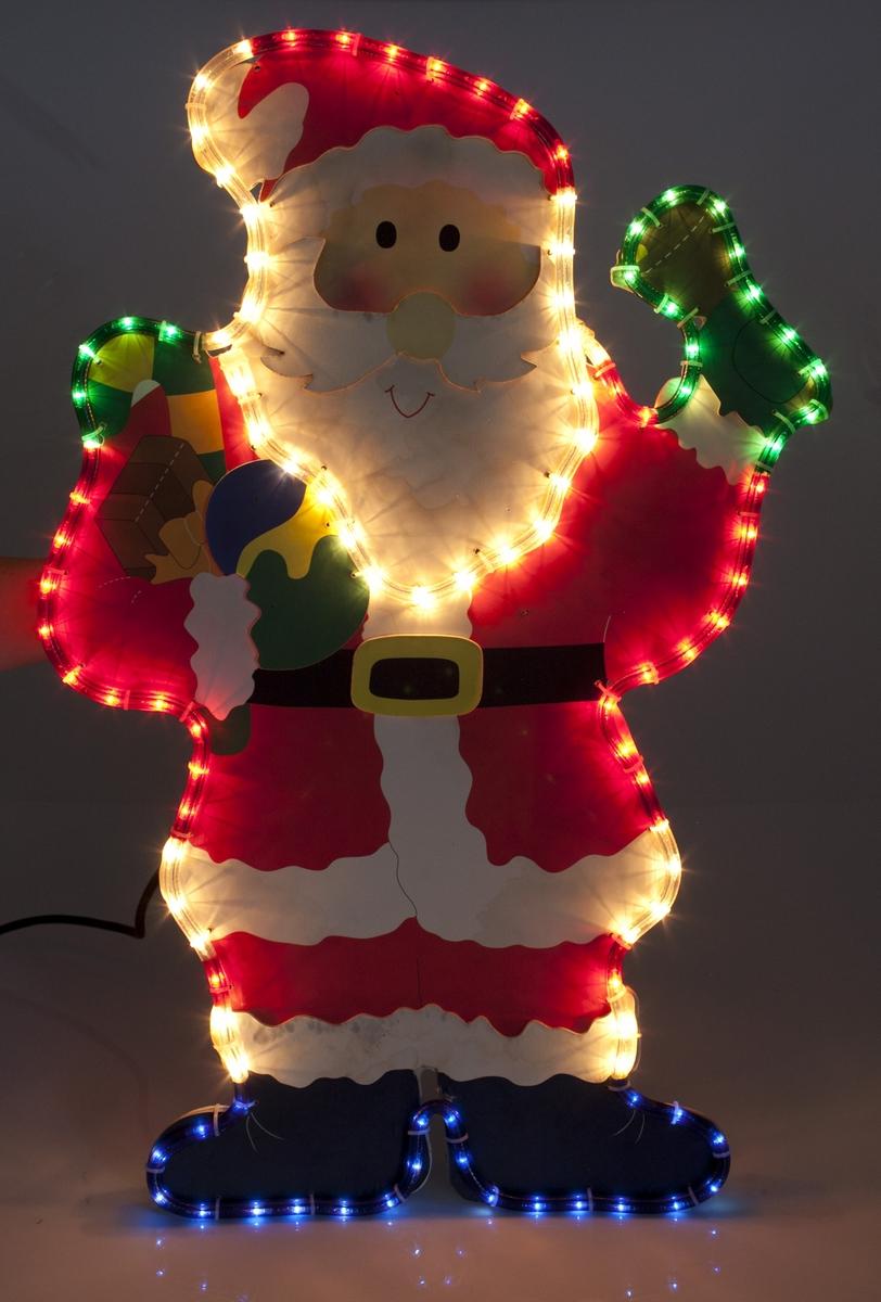 """Eske med fotografi av julenisse med ropelight på grønn bunn. Esken er hvit  Tekst på eske (tre skandinaviske språk):  Forside: Julefigur for utendørs bruk, med flerfarget """"rope light""""  Bakside: Julefigur for utendørs bruk, med flerfarget """"rope light"""". for trygg og sikker drift bør du lese nedenstående opplysninger nøye: Bruksanvisning: Spesifikasjoner: diameter 10 mm, normal lyspære 6,5 V 0,324 W....Ledekabel 2 m, Artikkel nr.: CYR6038-7  Made in China"""