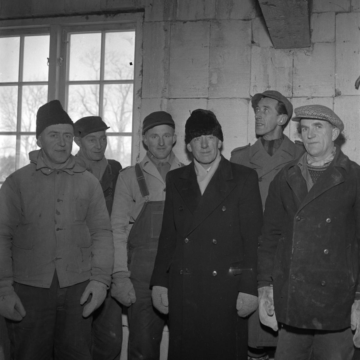Interiørbilde med gruppeporttrett. Aust-Agder-Museets første byggetrinn  - senere arkivfløy -  på Langsæ.  Kranselag. Gruppeportrett med håndverkerne.  Albert Ugland  -  foran i midten.