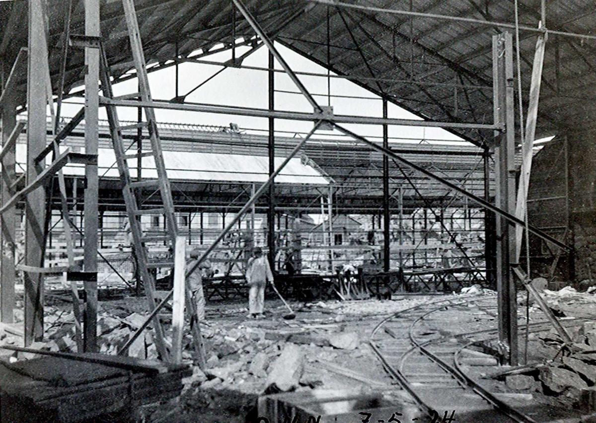"""""""07/05-1924"""" Nitriden. Bygging av stekeribygning for steking av elektrodekull. Jernkonstruksjoner. Gjennom konstruksjonene skimtes Omformerstasjonen. Skinnegang for intern transport med traller. Bildet er tatt fra kaianlegget"""