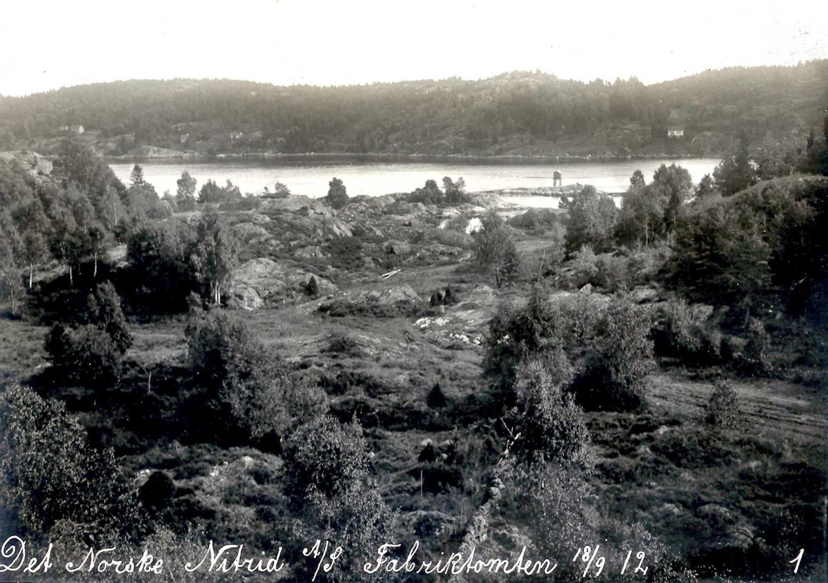 """""""18/09-1912"""" Nitriden. Tomtevalg for fabrikken. Her blir ovnshusene og omformerstasjonen plassert. Kupert terreng og dyrket mark inni mellom. Fyrlykt nr. 612 i Norsk Fyrliste, plassert i 1894, senere, i 1929, flyttet til Friisøy lenger vest. Tromøysund og Tromøy."""