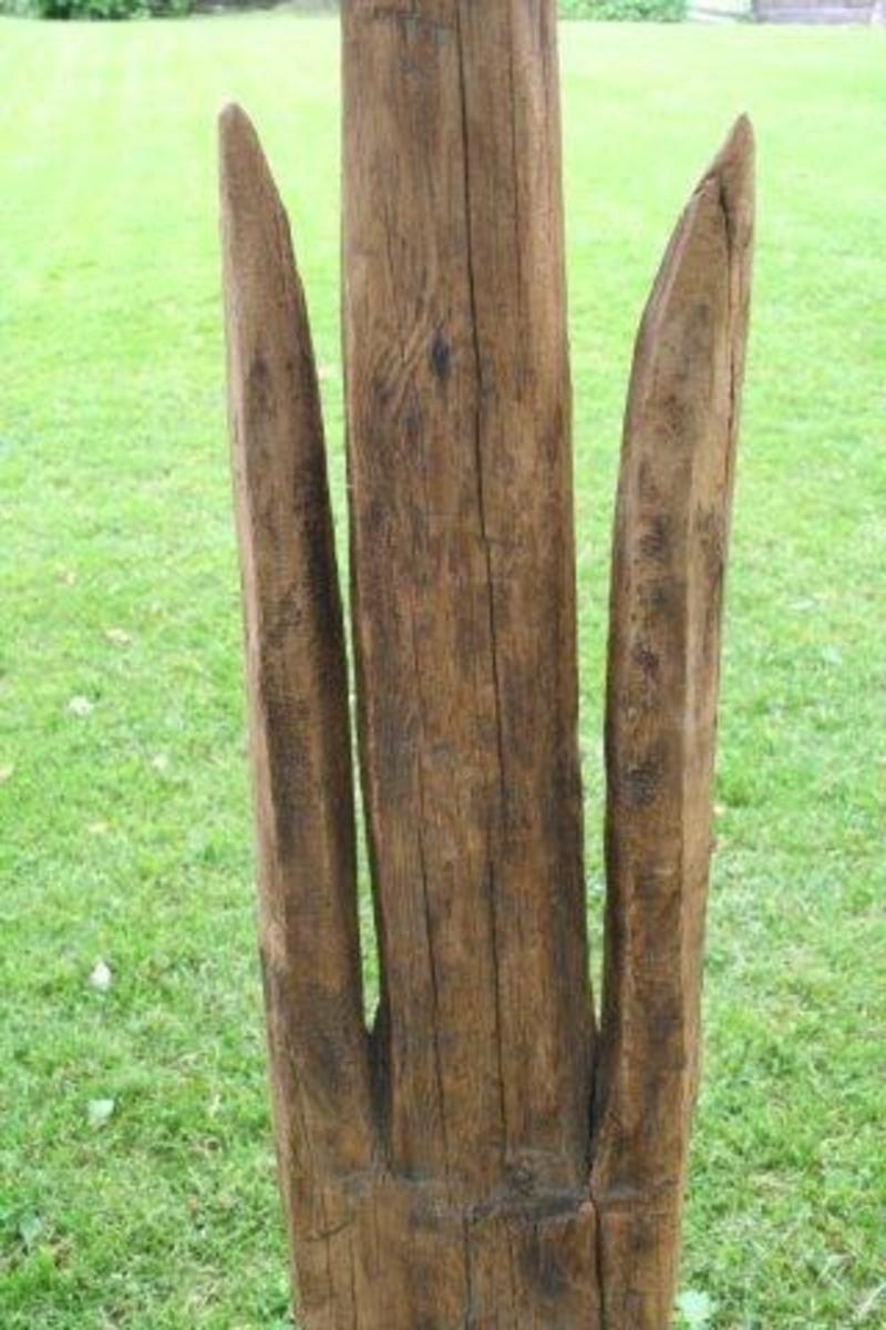Form: Smal planke med 3 spisser - den midtre høyest. Kileformede spalter mellom spissene.