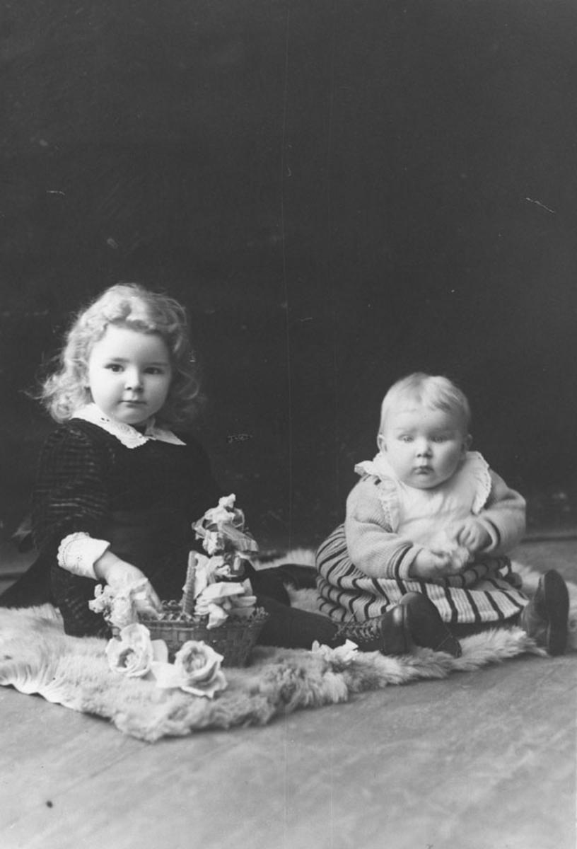 To små barn sittende på et teppe