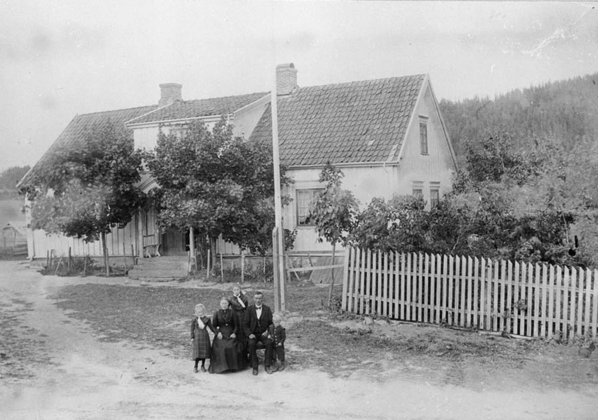 Flokk mennesker oppstilt på en gårdsplass ved en flaggstang.
