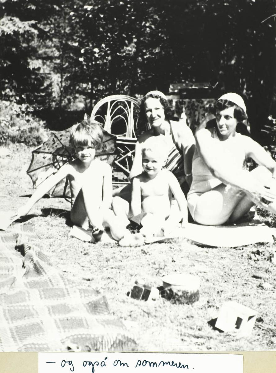Fire personer, to barn og to voksne sittende utendørs