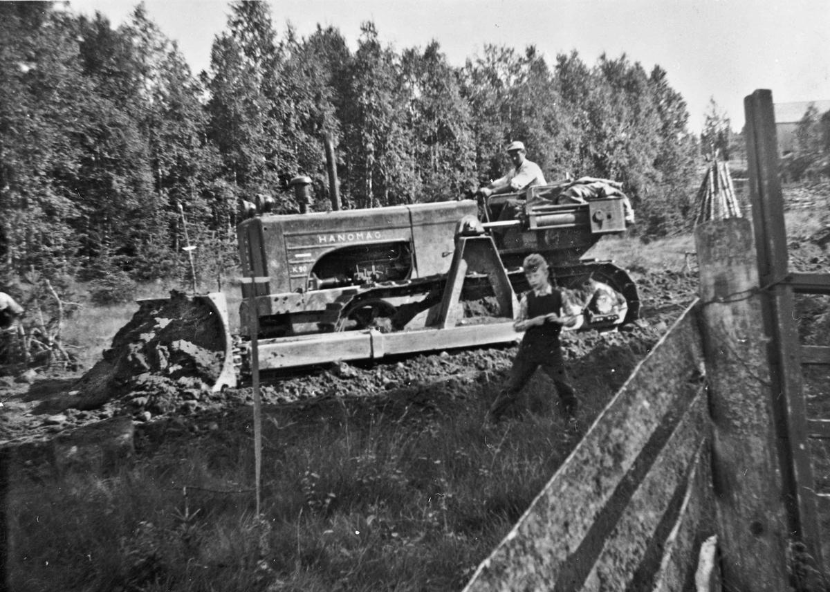 Veibygging Hoelseter – Gresslien i 1954. Oddvar Millidal sitter på bulldozeren. Gutten heter Knut Arne Hjerpseth.