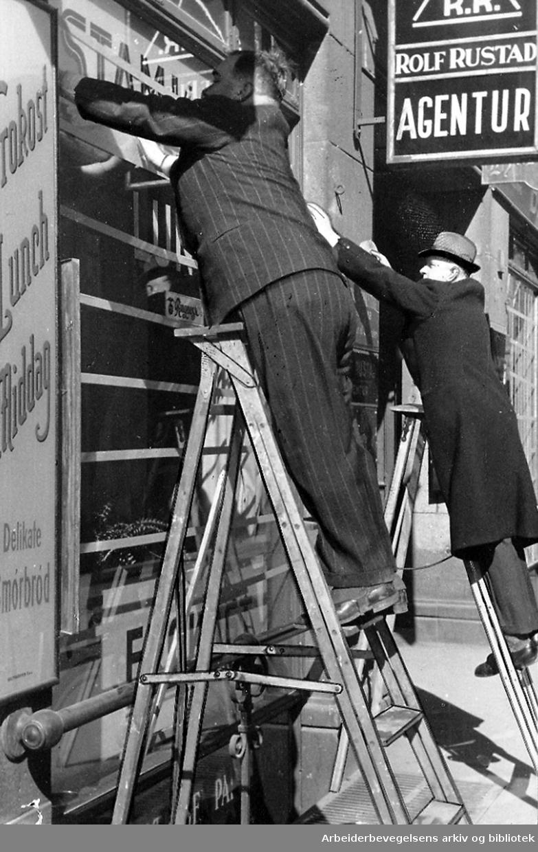 Butikker forbereder seg på at byen kan bli bombet, og dekker til vinduene,.13. april 1940