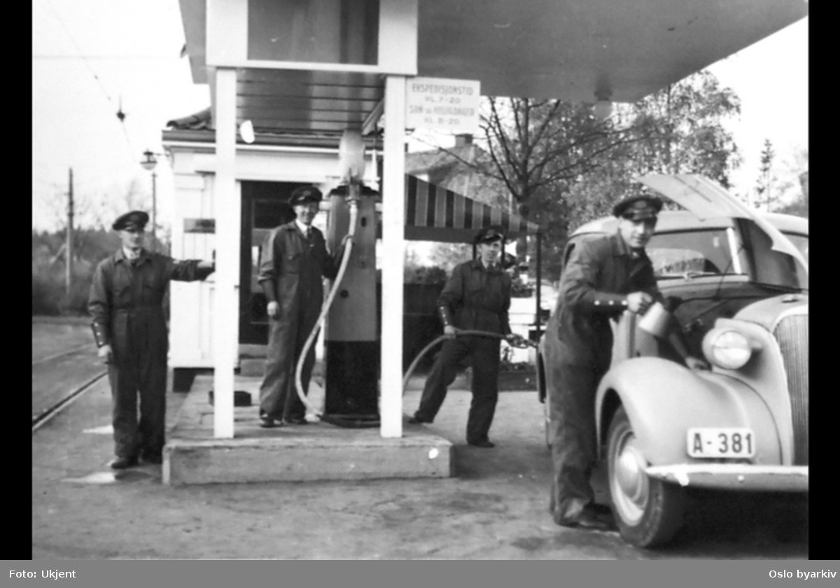 Arbeidere fyller bensin og poserer