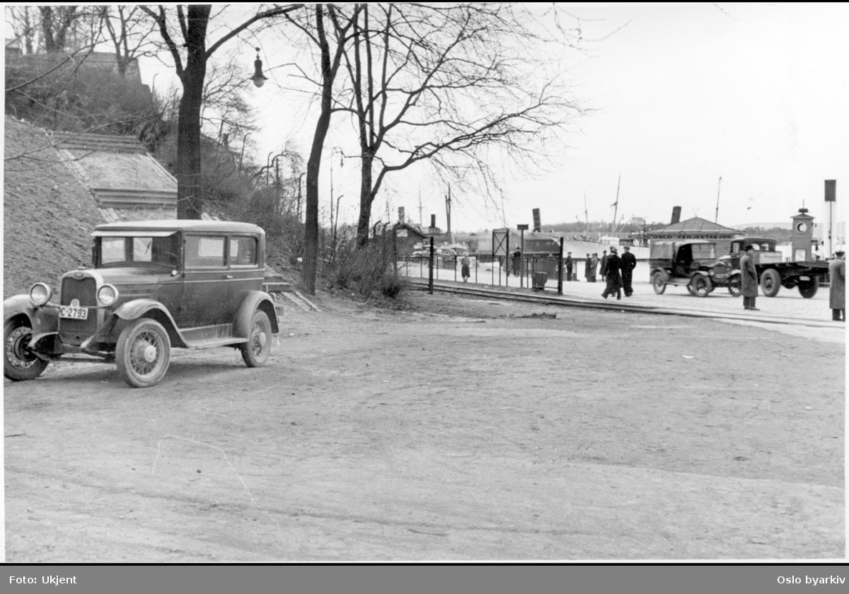 Bil på Tordenkiolds plass (nåværenede Rolf Strangers plass), nedenfor restaurant Skansen. Rådhusplassen. Akershuskaia med lastebiler og bryggeskur i bakgrunnen. Parkert bil.