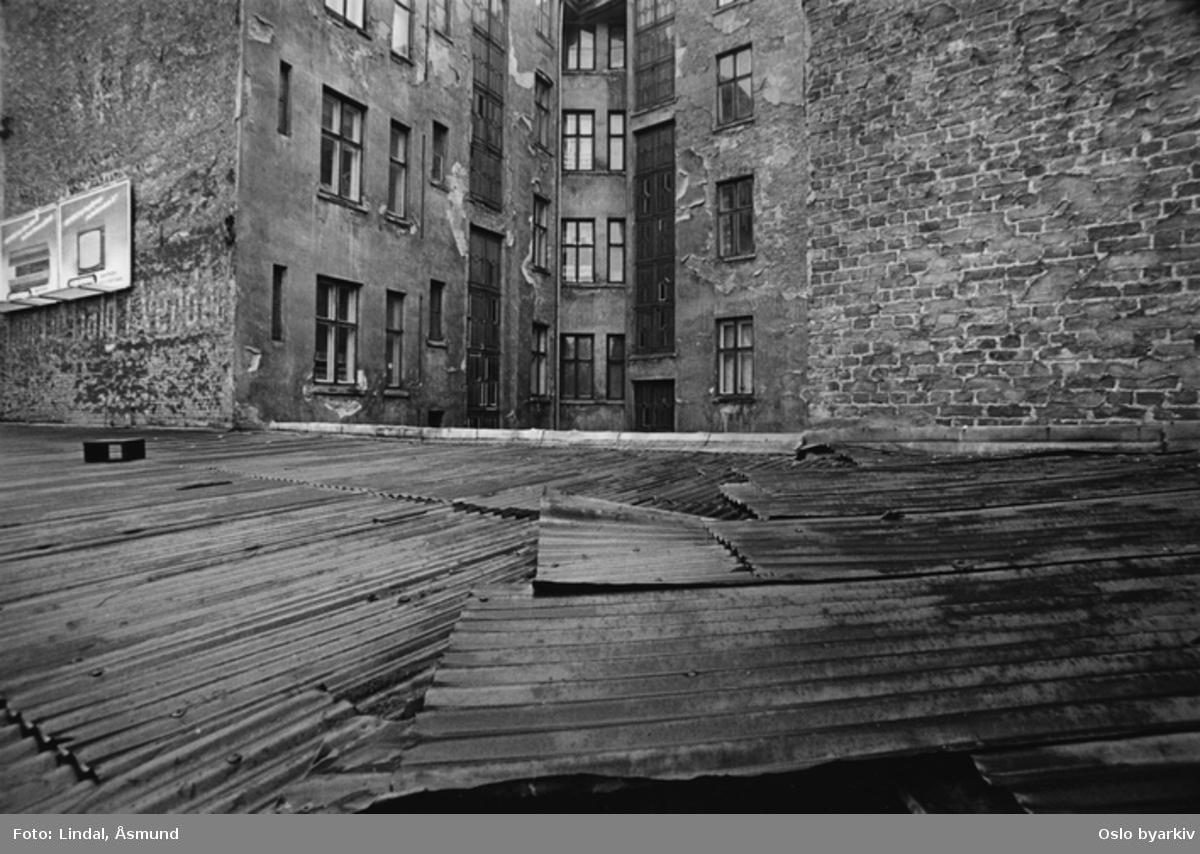 Utsikt mot bakgården. Bølgeblikktak. Reklame på veggen. Fotografiet er fra prosjektet og boka ''Oslo-bilder. En fotografisk dokumentasjon av bo og leveforhold i 1981 - 82''. Kontakt Samfoto ved ev. bestilling av kopier.