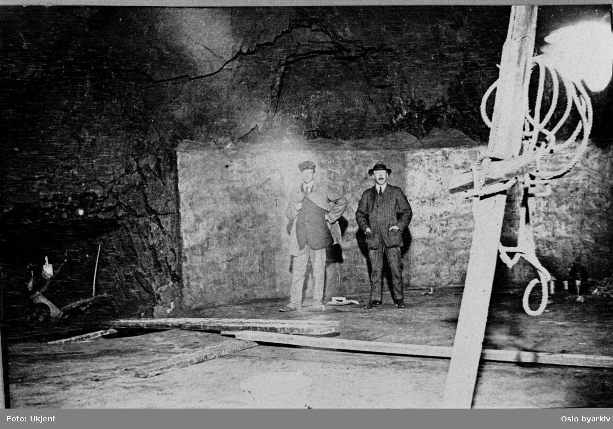 """Ledere innen vannvesenet i ene kammeret i drikkevannstunnelen. Oppmuret vegg og gulv. Albumtittel: """"Akers Vand- og Kloakvæsen Fotografier af Anlæg"""""""