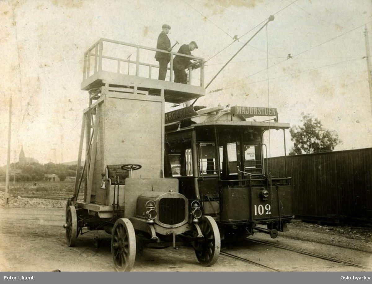 Blåtrikkens tårnbil utfører service på en av Majorstulinjens trikker. Fra venstre Gustav Falch, til høyre Chr. B. Falch. Bildet er tatt rett utenfor vognhall 3. I bakgrunnen ser vi Vestre Akers kirke. Området er fortsatt ikke bebygd.