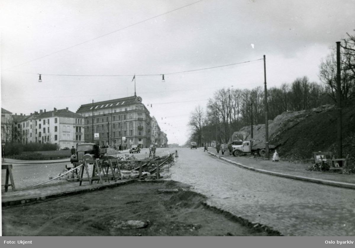 Utbedring / senkning av trikkeskinner (bue) fra øverst i Stortingsgata opp mot Drammensveien ved Abelhaugen. Lastebiler. Triangelplassen, nåværende 7. juni plass, til venstre.Bildet er trolig fra perioden 1947-50 i forbindelse med flytting av trikkesporene. Omleggingen foregikk i to omganger, først vestgående spor, deretter østgående spor.