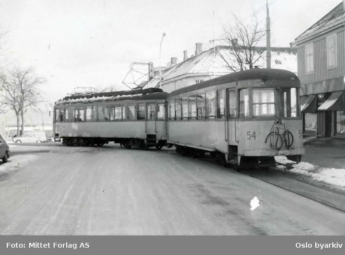 """Sporvogn med tilhenger tilhørende Trondheims Sporvei. To av Graakalbanens vogner på vei ut fra endeholdeplassen i St. Olavs gate rundt 1968. Vognsettet ble levert av Skabo i 1942 (motorvogn) og 1947 (tilhenger). Bildets origianle tittel """"Trondheim. Jernbanestasjonen"""" er feil."""