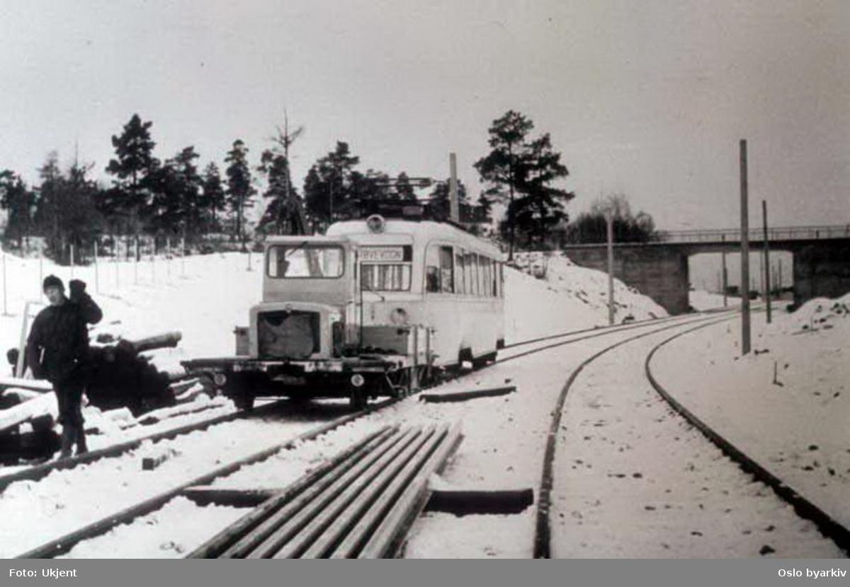 Oslo Sporveier. Trikk motorvogn 158 type Gullfisk B2 på vinterføre trekkes av Robeltralle ved Munkelia på Lambertseterbanen. Strekningen Høyenhall-Bergkrystallen satt i drift i 1957 med bytrikker fra linje 4, Kjelsåsbanen. (T-banedrift fra 1966.)