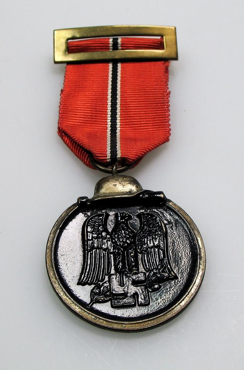 """Østfrontmedalje.  Medaljen ble designet av SS-Scharfürer Ernst Kranse og ble opprinnelig kalt """"Medaille Winterschlacht im Osten 1941/42"""".  Ble kun båret som stripe i 2. knapphull når det ikke var parade.  Har tilhørt sjef for Rikshirden, Thorvald Throndsen.  Gave fra datter Ellen Raastad."""