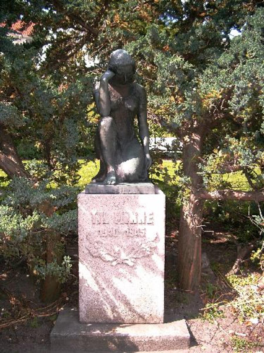 Kvinne i bronse på granittsokkel.