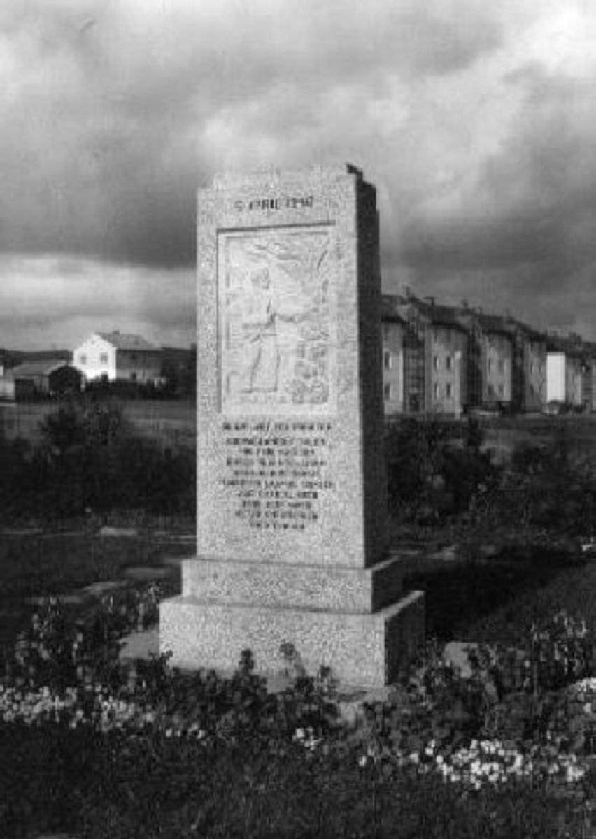 Minnestøtte med relieff. Navn hugget inn på forsiden og 8. mai 1945 på baksiden. Granitt.