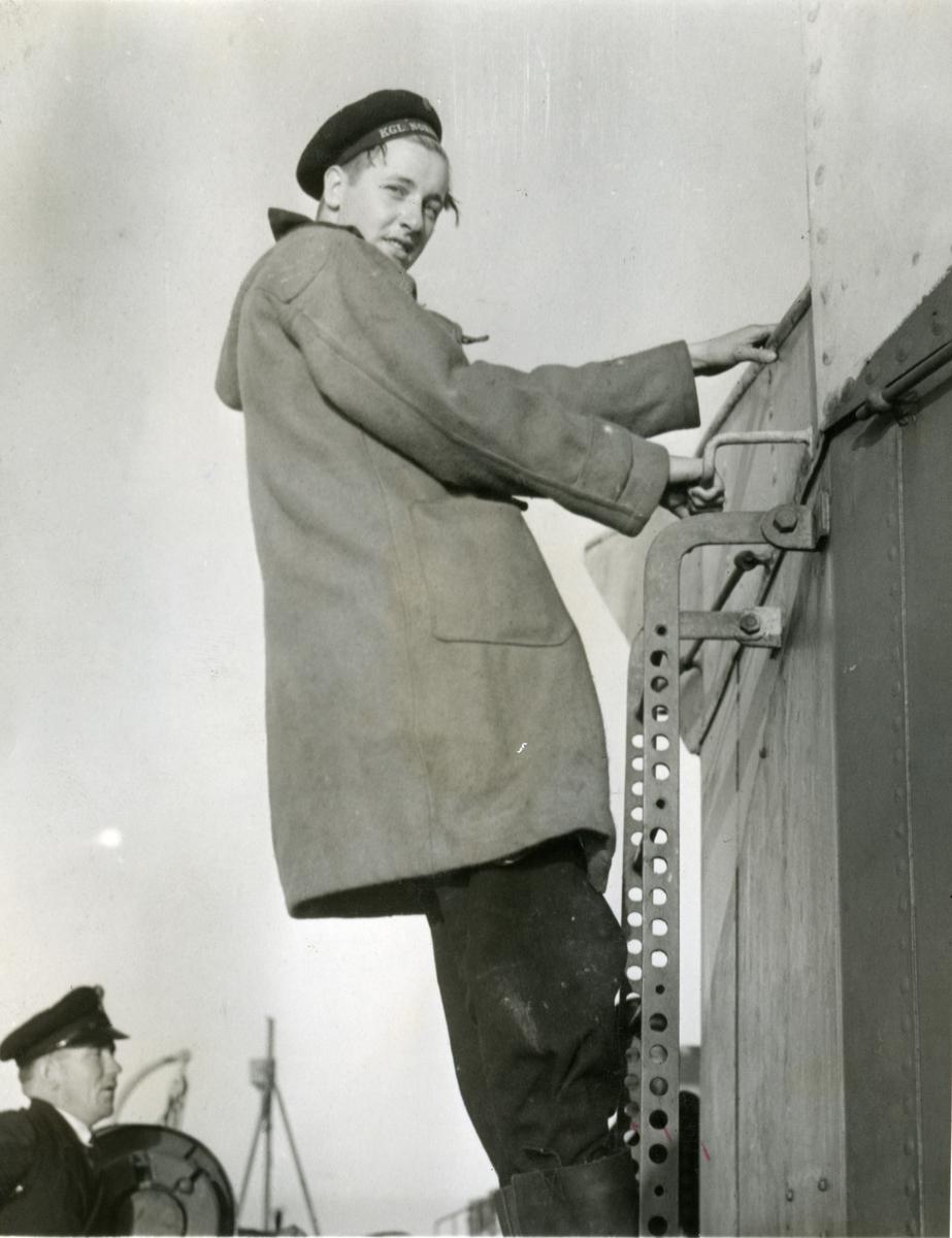 """Album Glaisdale H.Nor.M.S. """"Glaisdale"""". Fotograf: Keystone press. En av mannskapet klatrer stige."""