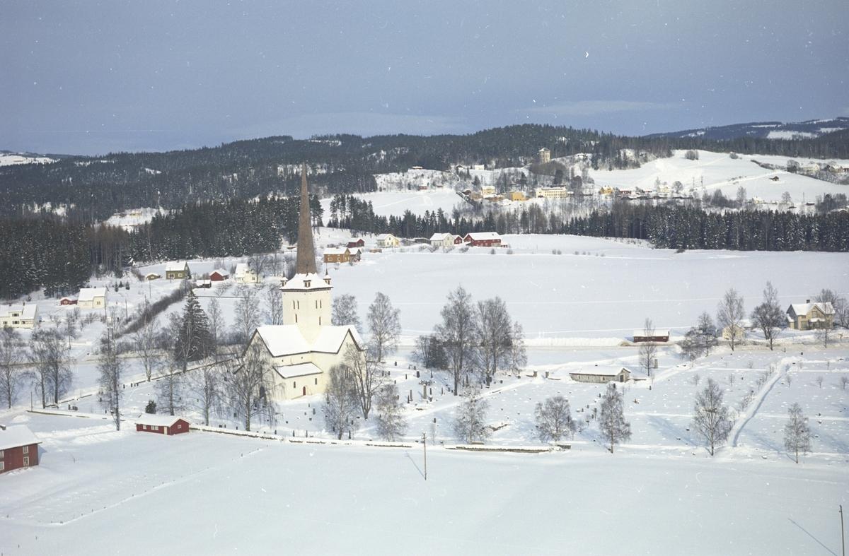 Flyfoto av Ringsaker kirke og omegn. Ringsaker Folkehøgskole i bakgrunn. Vinter.