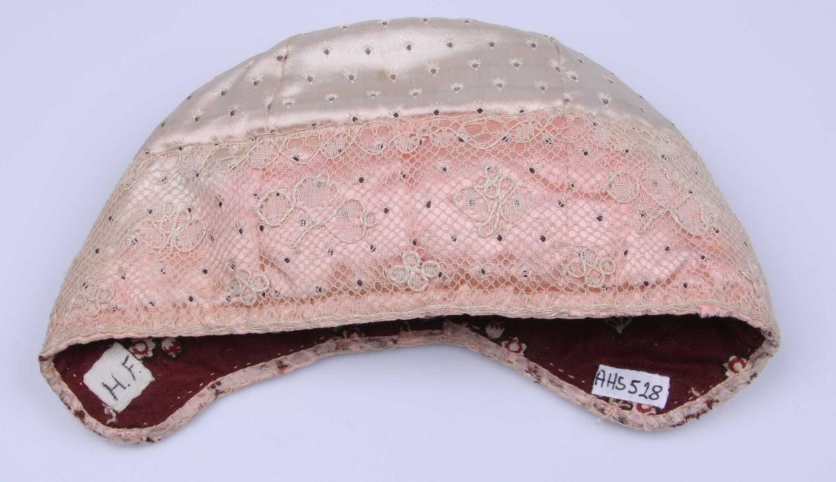 Av rosa atlask med lite, dekorativt mønster i lyserødt og sort. Luen består av fem deler: Tredelt forstykke og todelt nakkestykke. Kantet med rosa silkebånd og påsydd en 6,2 cm. bred knipling av Mechlin type med kantbord med picoter og strøblader av meget enkel form. Fôr av bomullstøy med trykt mønster: rødbrun bunn, små hvite blomster med mørkebrun kontur og litt rødt i blomsten, og gulbeige blader. Mellomfôr. Spor etter knytebånd.