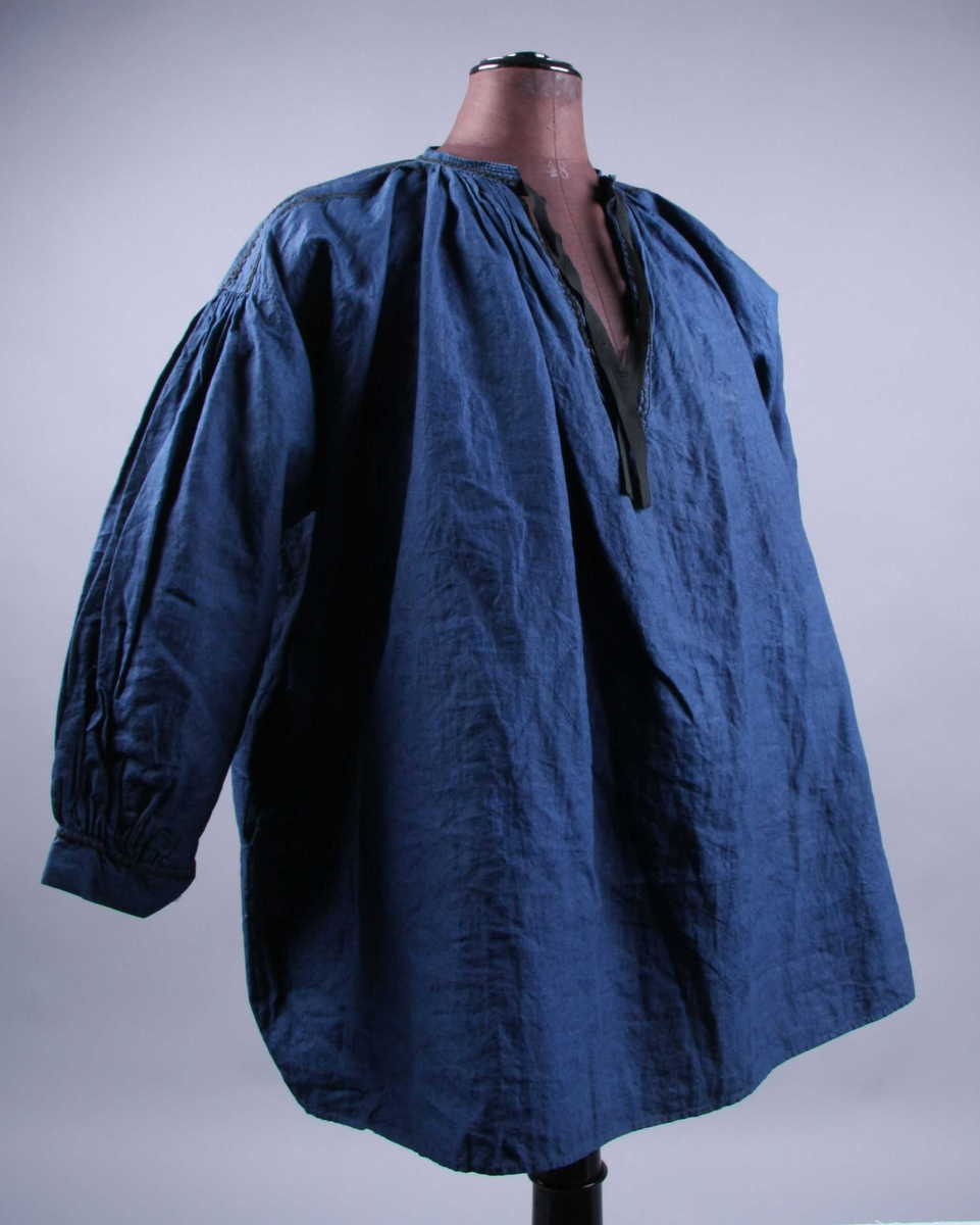 Av blå lin i ett stykke lagt dobbelt med søm i sidene. Skjorten har et 6,5 cm. bredt bærestykke påsydd på skuldrene og er tett rynket i halsen med en smal linning, 1,8 cm. bred. Linningen er matelassert med tre snorer øverst og er brodert med gren-søm i sort. Splitten foran er 22 cm. lang og har utvendig belegg med brodert sort sikksakk-bord. Samme slags broderi i tre rader på skulderstykket, den midterste med punkter i vinklene. Ermet er rynket midt oppe på skuldrene med innfelt firkant under armen. Tett rynket til en 4 cm. bred linning nederst. Porselensknapp og knapphull og 6,5 cm. splitt langs sømmen. I sidesømmene, 20 cm. fra underkanten er satt inn en stikklomme på hver side. Smal fall nederst på skjorten, alt håndsydd.