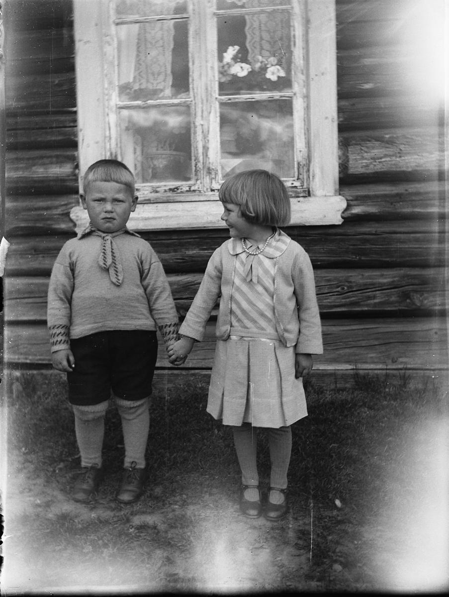 To ukjente barn holder hverandre i hendene foran et ukjent hus.