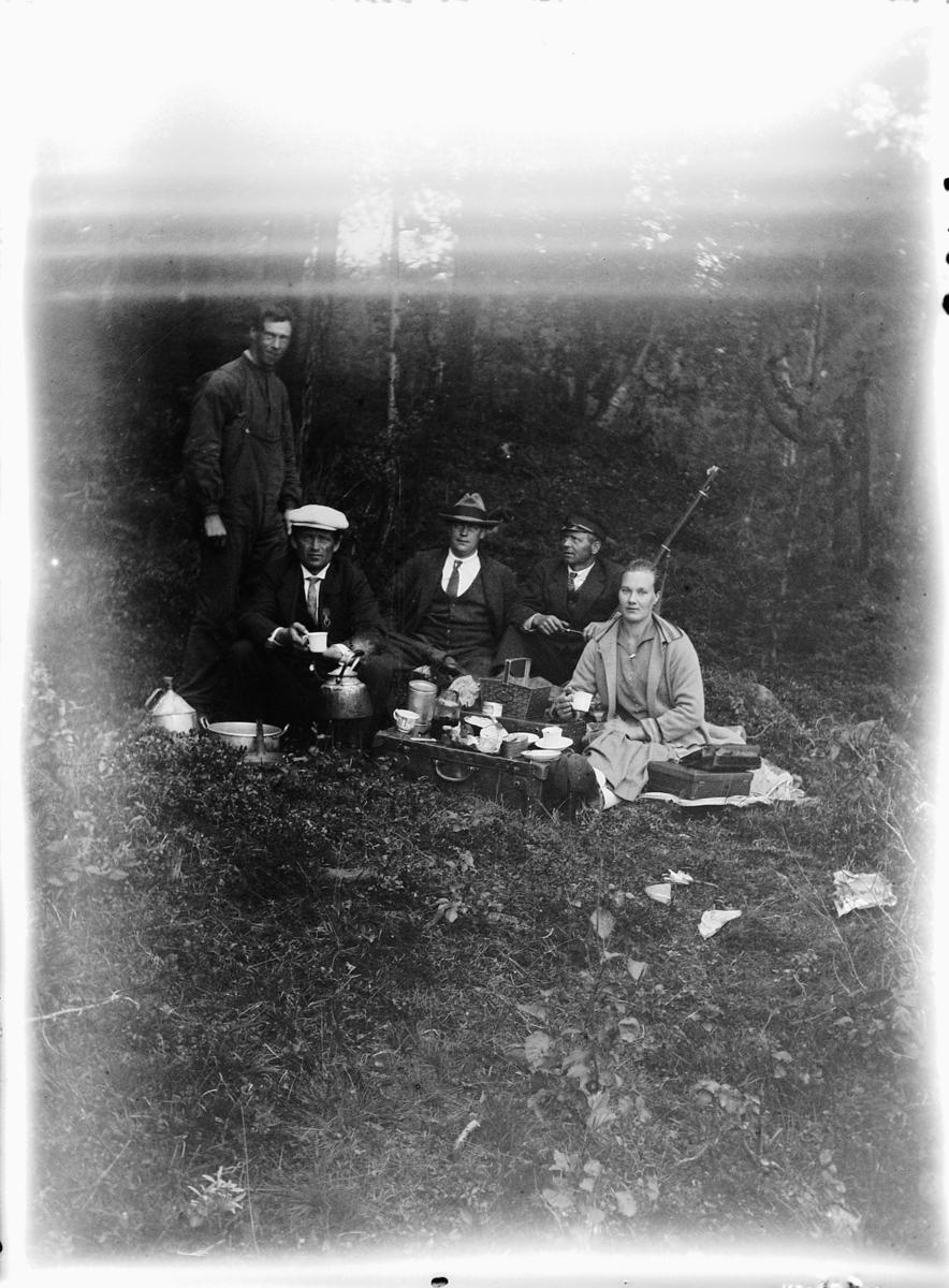 Fem ukjente personer på tur i skogen. Kaffe, kaffekjele, gevær.