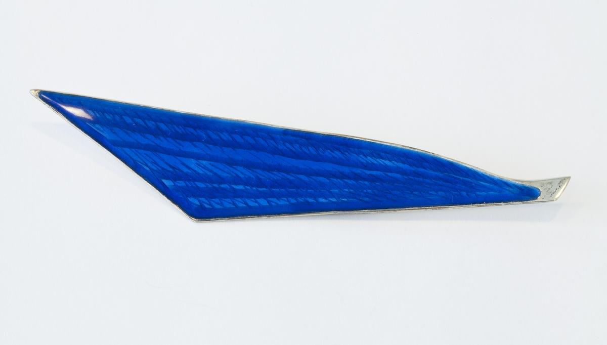 Brosjen er formet som et seil. Den er gjort sterling sølv og har blå emalje. Ingraveringene i sølvet, et slags rutermønster under emaljen, skinner gjennom.