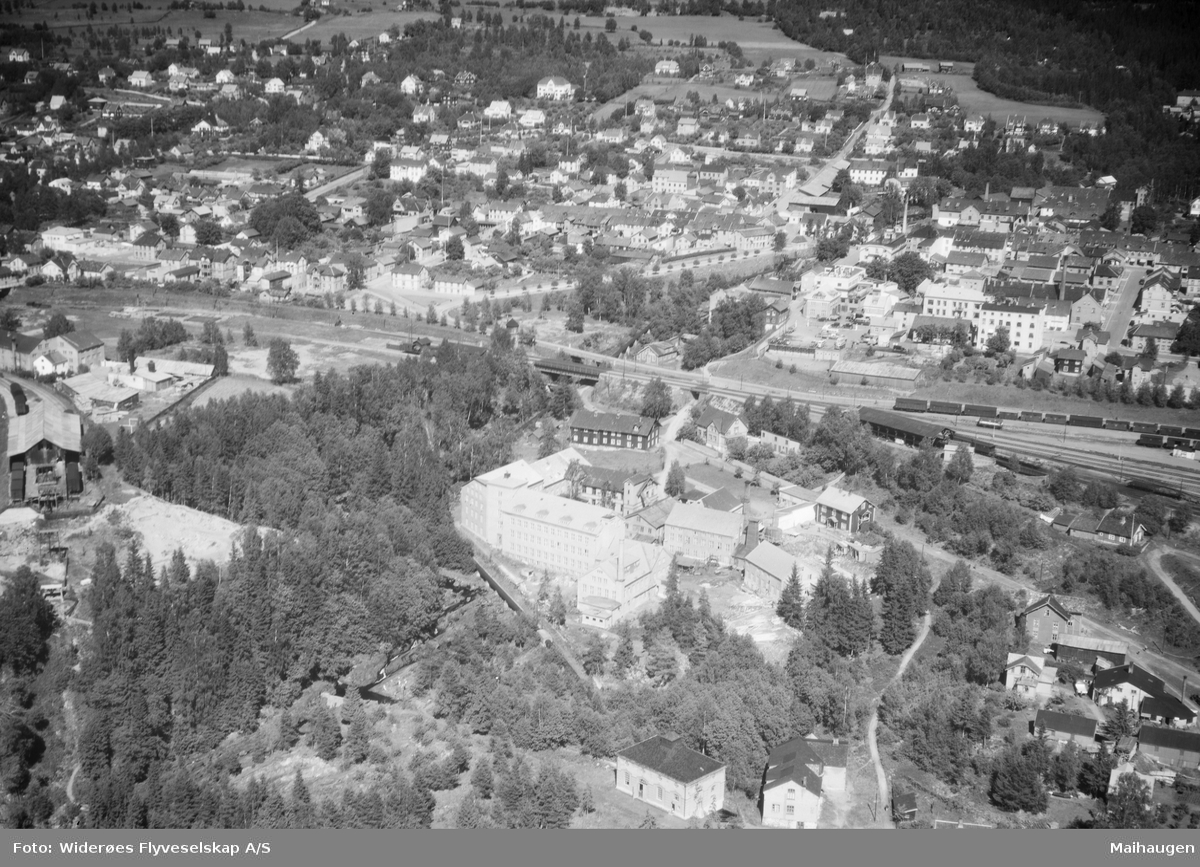 Flyfoto, Gudbrandsdalens Uldvarefabrik A/S, mot Lillehammer sentrum nord, del av jernbanestasjonen helt til høyre