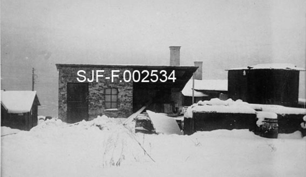 Fra de nye produksjonsanleggene Schwencke & Co's Eftf. bygde på Børsholmen i Asker i 1924.  Schwencke & Co. var et firma som produserte og forhandlet bek og andre tjærebaserte produkter.  Nettopp i 1924 ble mye av produksjonen flyttet fra Kongshavn sør for Oslo til Børsholmen, hvor den ildsfarlige virksomheten kunne drives i betryggende avstand i forhold til annen bebyggelse.  Dette fotografiet viser noen av bygningene på anlegget.  Midt i bildet ligger et hus med pulttak.  Under den venstre halvdelen av dette taket var det et rom med teglsteinsmurte vegger.  På den veggen som vendte mot fotografen var det ei dør og et støpejernsvindu.  Under den høyre delen av det samme pulttaket later det bare til å ha vært et åpent skur da dette fotografiet ble tatt.  Til høyre i bildet ser vi et lavt murverk (kanskje en uferdig bygning) med en diger, vertikalstilt stålsylinder inni.  Bakenfor skimtes et par andre tak og et par skorsteinspiper.  Fotografiet er tatt på snødekt mark.
