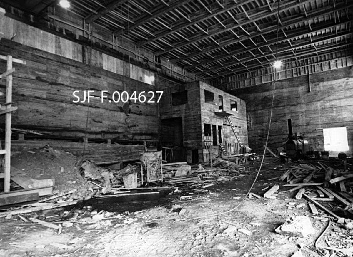 Interiør fra den uferdige industrihallen som ble reist vinteren 1965-66 med sikte på at den skulle romme nytt renseri og flishoggeri for Union Bruk i Skien.  Dette fotografiet bærer preg av å være tatt før byggearbeidet var avsluttet.  Forskalingene fra veggene, som var utført i armert betong, var riktignok demonterte, og takkonstruksjonen, et meget flatt sperretak, var på plass.  Vinduene var imidlertid ikke kommet på plass, alt produksjonsutstyret manglet fullstendig.  På golvet lå det jordhauger og materialrester.  Ved gavlveggen ser vi dessuten en lokomobilliknende maskin som antakelig ble brukt av anleggsarbeiderne.  I hjørnet mellom gavl- og langvegg var det støpt vegger til noe som antakelig skulle bli kontor (kontrollrom), muligens også garderobe- og toalettrom.