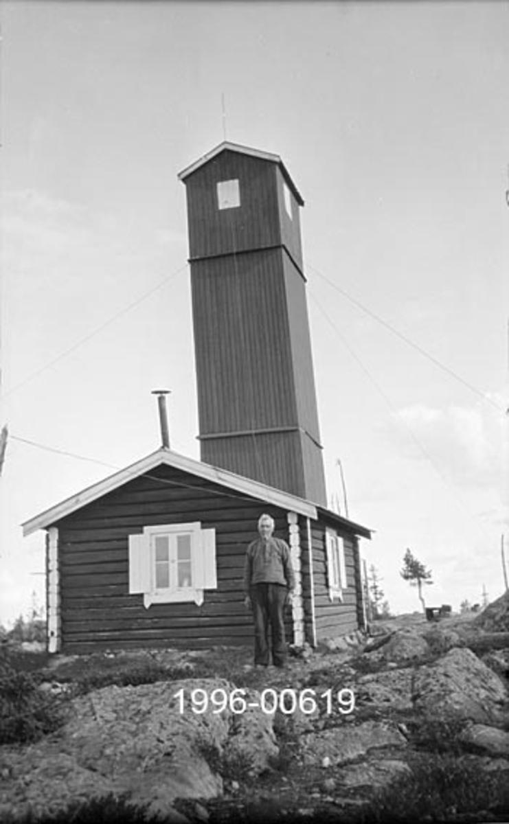 Knukberget skogbrannvaktstasjon i Stange allmenning i Hedmark.  Stasjonen ligger cirka fem og en halv kilometer sørøst for Espa jernbanestasjon og har utsikt over vide strekninger i Stange, Romedal og deler av Løten allmenniger.  Stange allmenning bygde anlegget.  Fotografiet viser hytta brannvakten bodde i og utsiktstårnet.  Hytta er laftet, har tilsynelatende ett rom og en etasje og saltak med bølgeblikktekke.  Bakenfor gavlen på hytta står et bordkledd, høyt tårn med kvadratisk grunnplan og saltak.  I den øvre enden av tårnet er det vinduer i alle himmelretninger.  Konstruksjonen er bardunert med sikte på å forebygge vindskader.  En mann, antakelig brannvakten, står ved hjørnet av vaktstua.   Brannvaktstasjonen på Knukberget ble ødelagt av brann i 1930, men seinere gjenoppbygd.  Fotografiet viser det opprinnelige anlegget, og er antakelig tatt i 1920-åra.