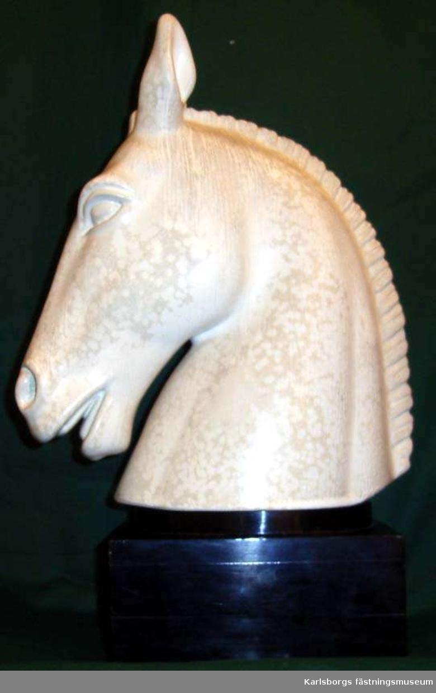 Hästhuvud på svart träsockel med inskriptionen Rörstrands hederspris i Nordiska ryttarspelen Skövde 1957. Hästhuvudet i keramik med marmorerad glasyr. Märkt Rörstrand G. Nylund Unik