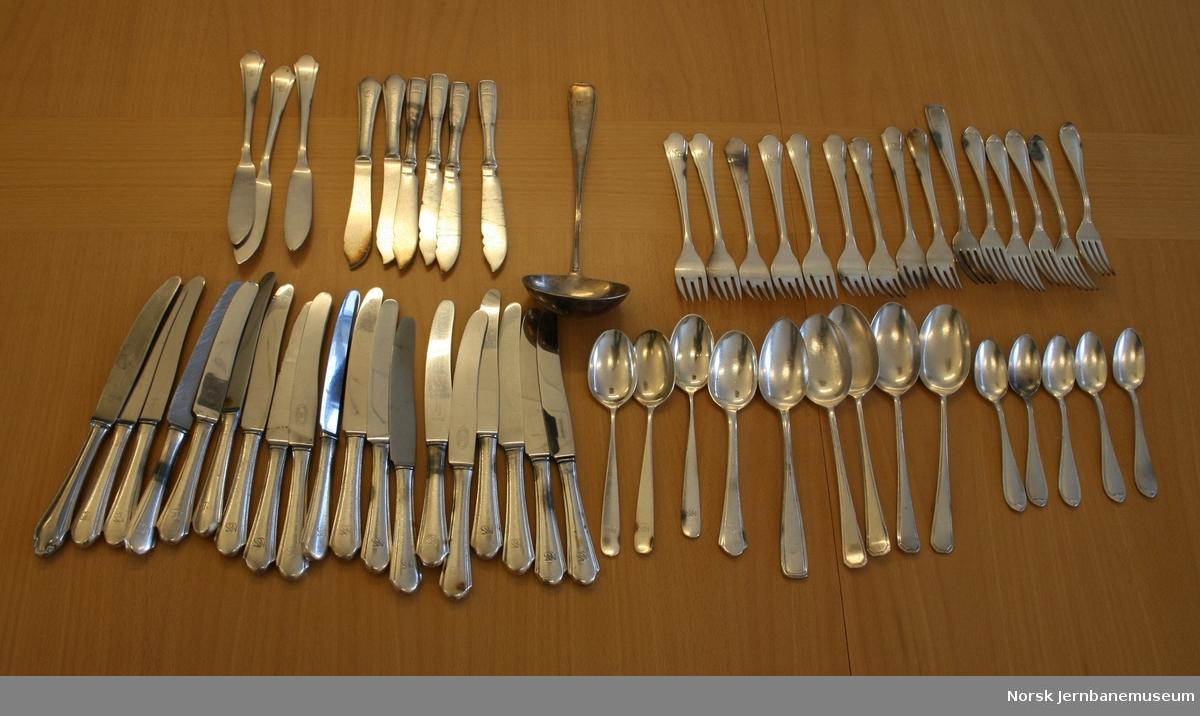 """Spisebestikk, de fleste med """"NSS"""" logo (Norsk Spisevognselskap), bestående av:  19 kniver, 6 kniver til fisk, 3 smørkniver, 15 gafler, 9 suppeskjeer, 5 teskjeer og 1 suppeøse. Alt bestikket er merket NM 90, som betyr 90 grams forsølving (Hotellplett)."""