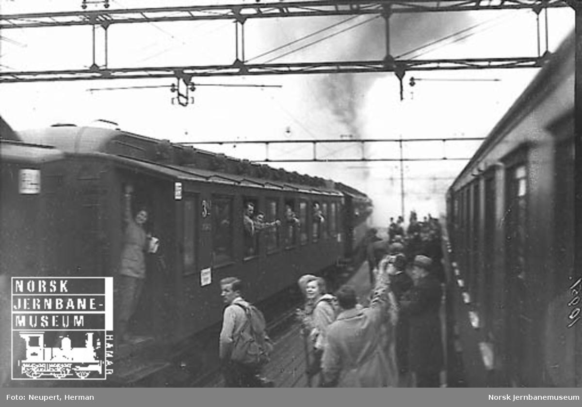 Reisende på plattformen på Østbanen i påsketrafikken; et tog forlater stasjonen