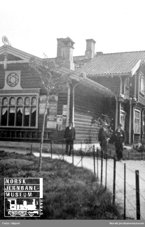 En samling menn utenfor Byglandsfjord stasjonsbygning