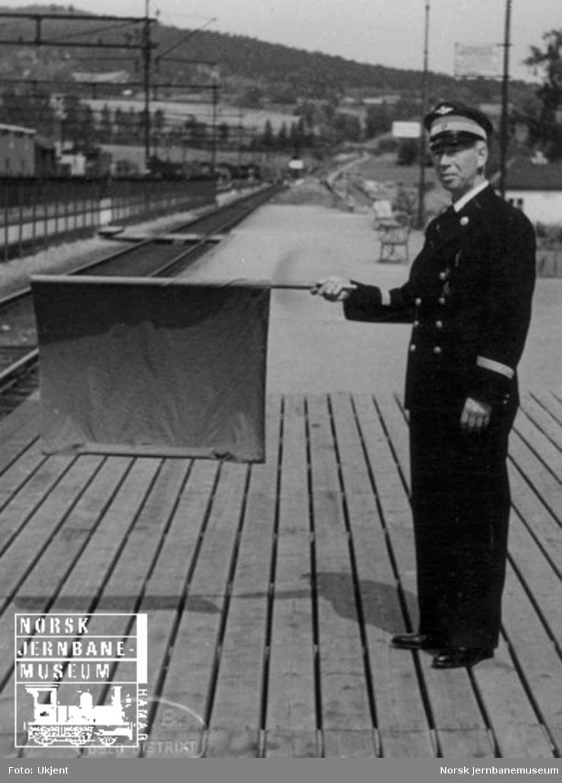 Togekspeditør gir stoppsignal med flagg