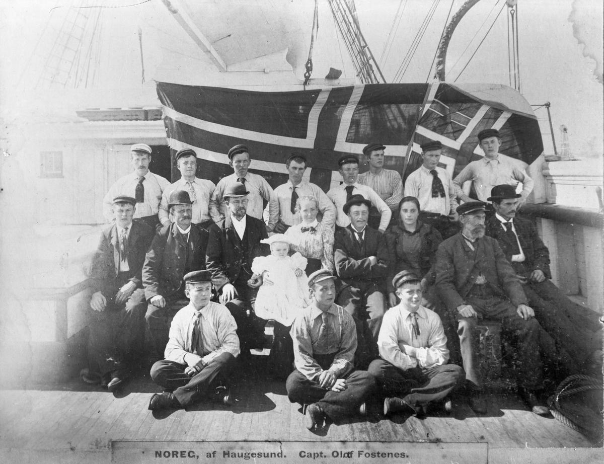 """Mannskapet ombord på skipet """"Noreg"""". Stort norsk flagg bak mannskapet. Midt på bildet sitter en kvinne med sin unge datter på fanget."""