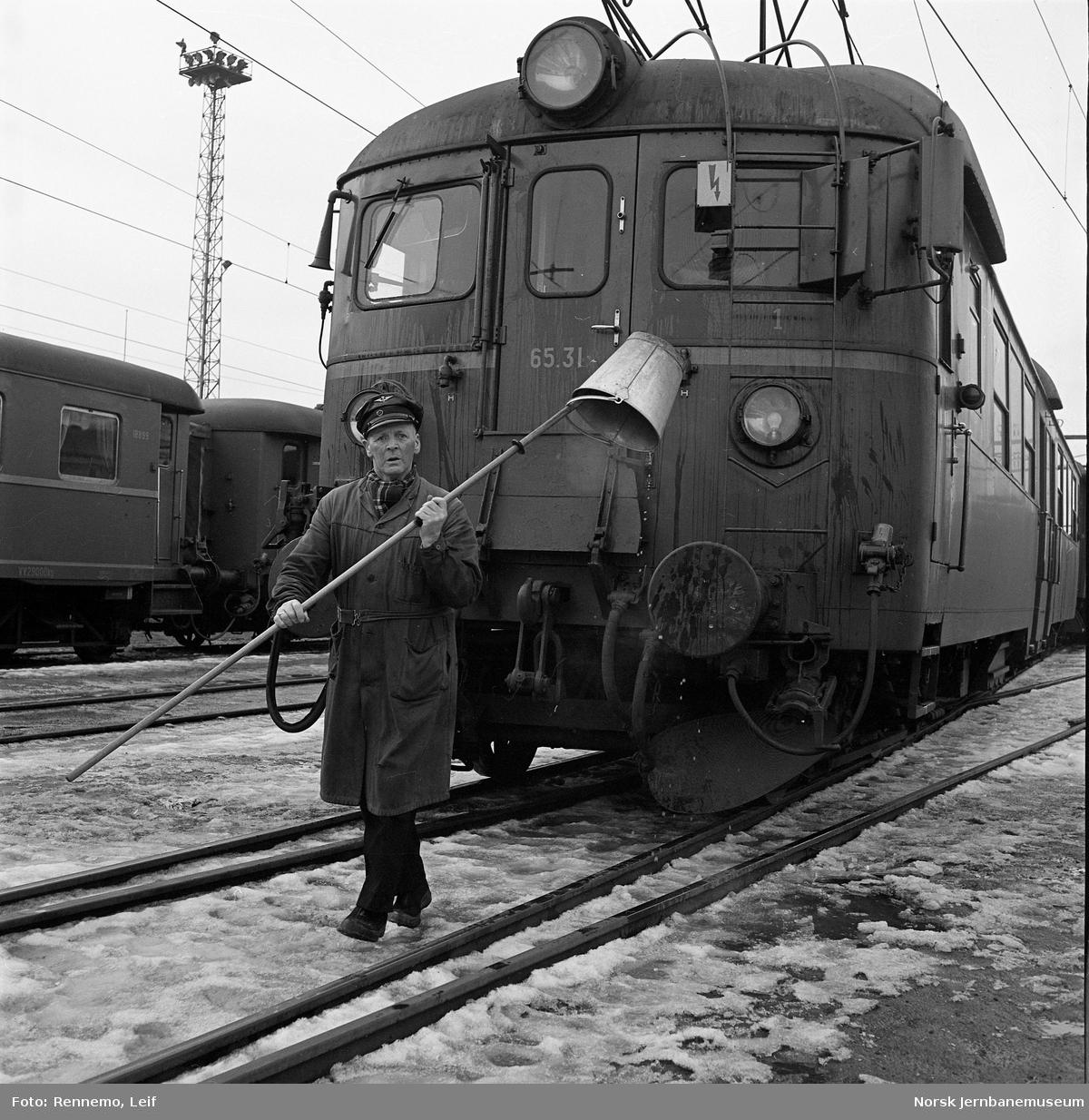 Motorvogn med jernbanemann som har pusset vinduene