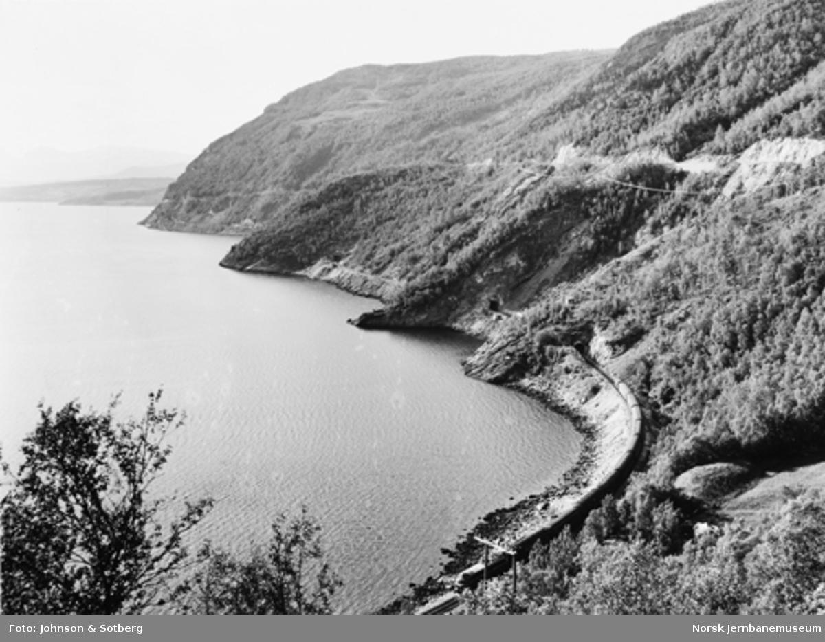 Oversiktsbilde over Nordlandsbanen mellom Rognan og Fauske med passerende persontog i Grytvika