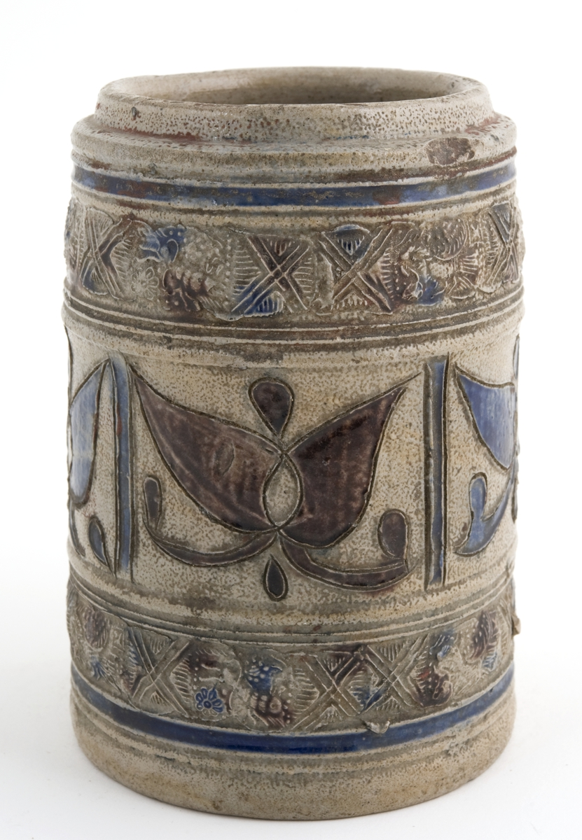 """Krus i grå keramikk av en type som stammer fra Westerwald-området i Tyskland. Karakteristisk er risset og stemplet dekor og pålagte relieffer, farget med koboltblå og senere også manganfiolett, under en klar saltglasur. Dette lave, sylinderformete kruset kalles """"Humpen"""" og ble masseprodusert gjennom hele 1600- og 1700-tallet."""
