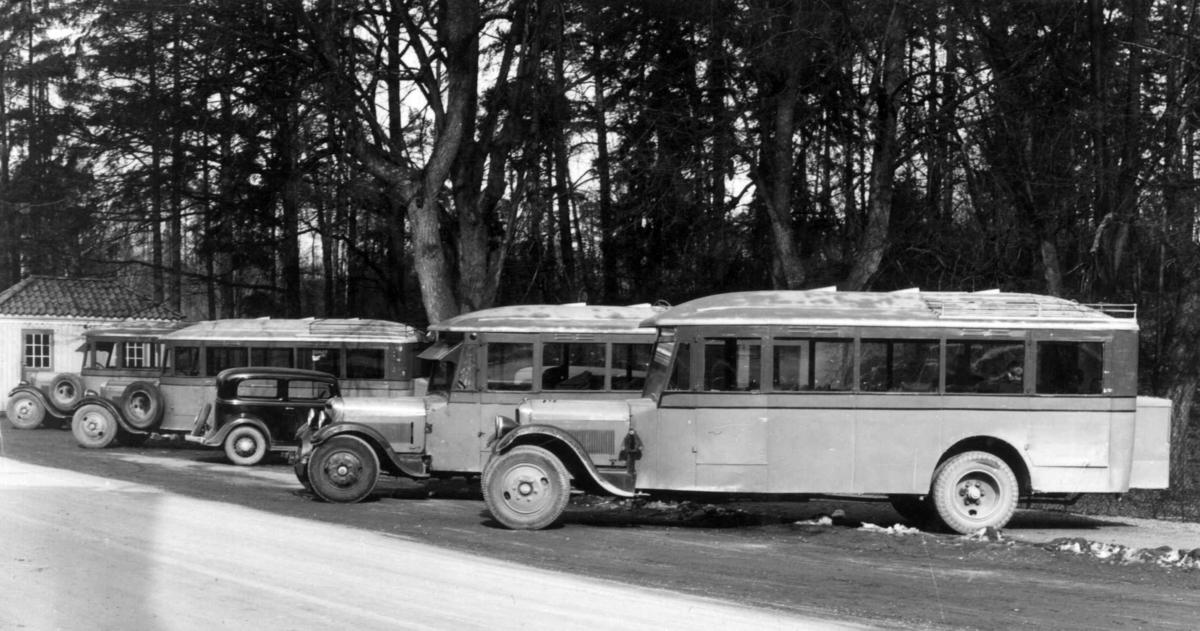 Busser parkert i veikanten utenfor hovedinngangen til Norsk folkemuseum. Første Vårbud 21. Mars 1934. Bussene er Ing. Schøyen Bilcentralers Studebaker 1928 med dører for sjåfør og (bakerst) nødutgang, samt tre tre små oppbygg for ventilasjon på taket. Opplysninger fra Asbjørn Rolseth. Bilen er en 1933-34 årgang av ukjent merke (ikke Ford).