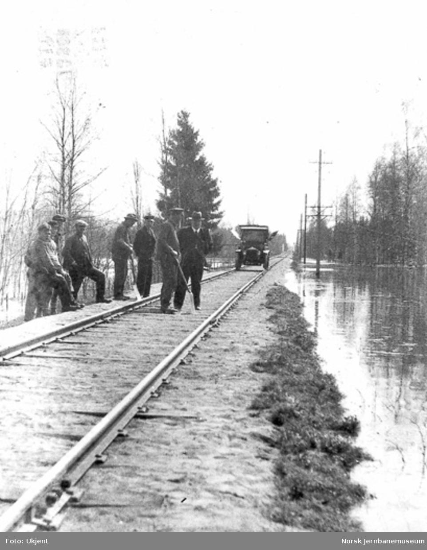 Banemannskaper og folk fra Hamar distrikt ved befaring på Rørosbanen ved flommen i 1934; distriktets inspeksjonsbil i bakgrunnen